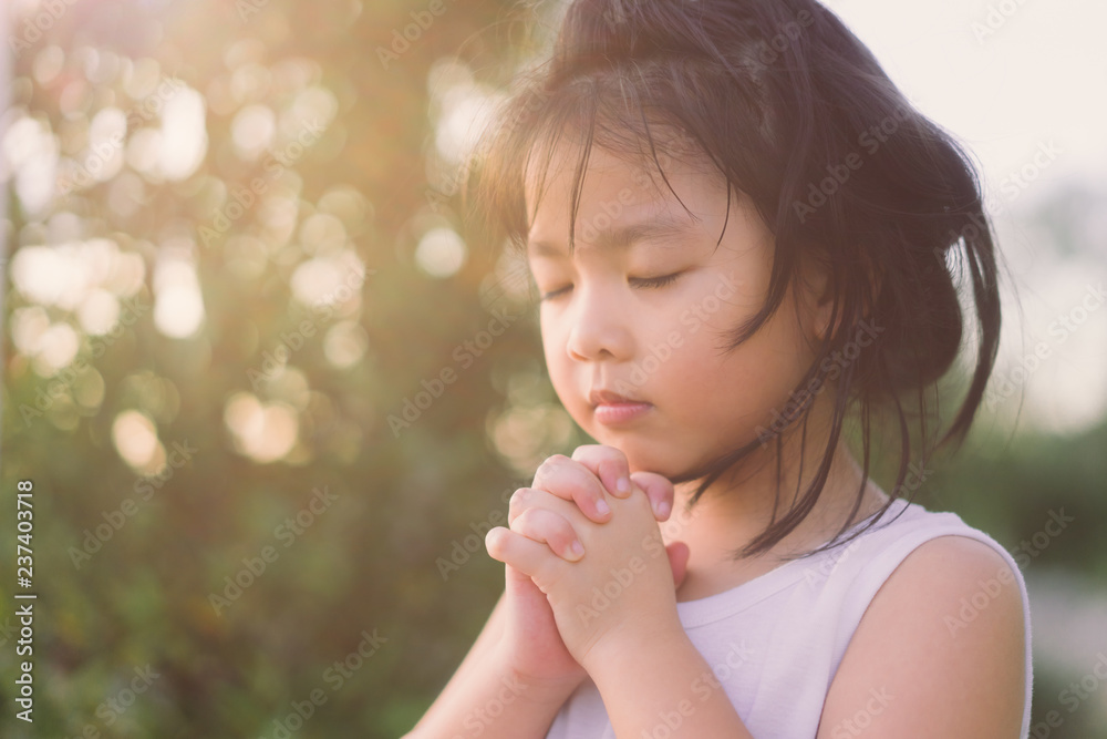 Fototapeta Little girl praying in the morning for a new day.Little asian girl hand praying for thank GOD,Hands folded in prayer concept for faith,spirituality and religion.