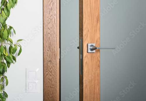 Photo Close-up of ajar door. Steel door handle, dark textured wood