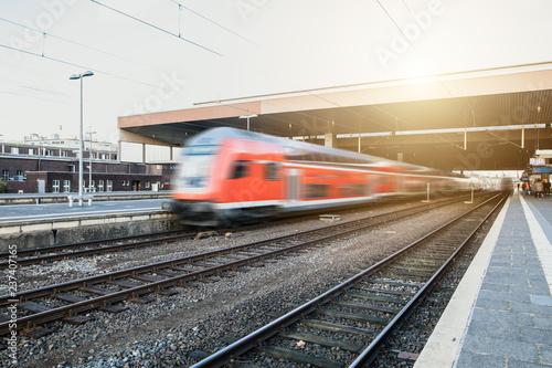 Spoed Foto op Canvas Spoorlijn Bahn fährt über Schienen am Bahnhof