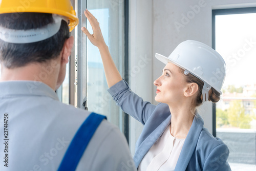 Fotografía  Architect woman and construction worker checking windows on site
