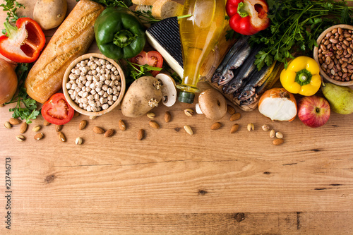 Healthy eating. Mediterranean diet. Fruit,vegetables, grain, nuts olive oil and fish on wooden table. Top view. Copyspace