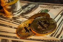 Three Coins In The Form Of Bitcoin On A Pile Of Dollars