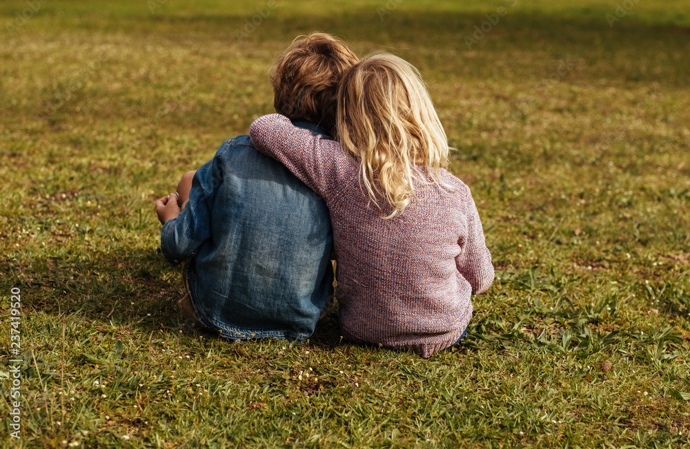 Fototapety, obrazy: Siblings sitting on the grassy lawn