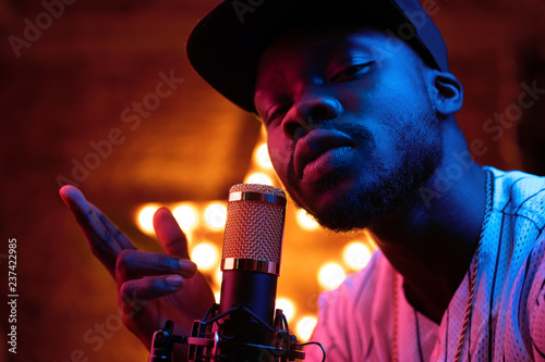 Photo Young man with beard and mustaches in baseball cap and t-shirt sing in microphone and look in camera