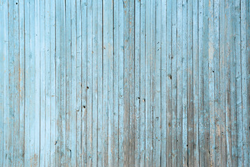 Wall of blue wooden slats. Exfoliated blue paint. Vertical laying, upright
