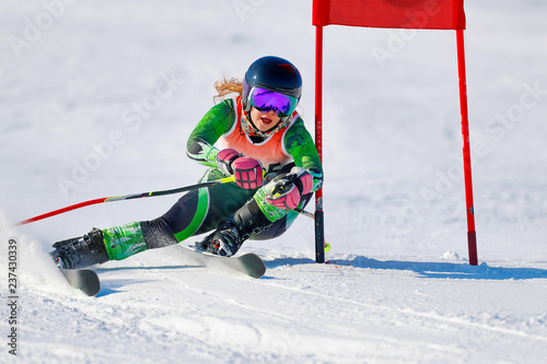 An alpine skier at a gate during a giant slalom race.