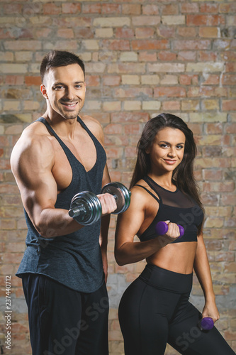 Fototapety, obrazy: Fitness couple - woman and man with dumbbells in gym