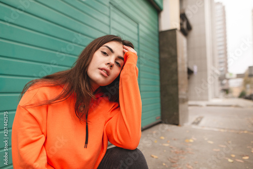 Fotografie, Obraz  Street portrait of a stylish girl in an orange hoodie, sitting on the street and posing on the camera