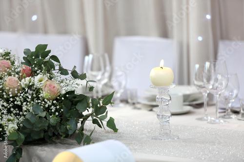 Fototapeta Biała świeca i bukiet kwiatów na białym stole. obraz