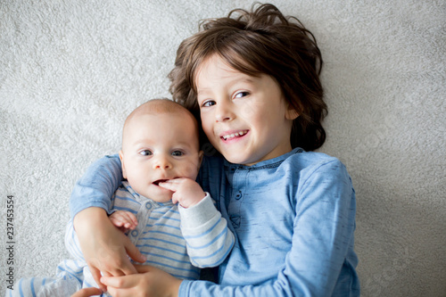 Happy brothers, baby and preschool children, hugging at home on white blanket