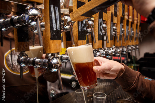 Staande foto Bier / Cider Hand of bartender pouring a red ale from tap.