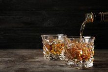 Pouring Whiskey From Bottle In To Glass With Ice Cubes On Table. Space For Text