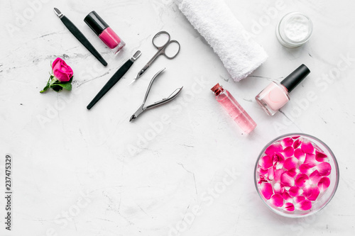 Fotografía tools for manicure with spa salt and rose on white stone background top view spa