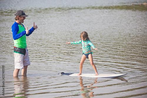 Surfschool, Vater bringt Tochter das Surfen bei