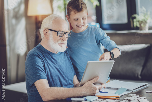 Attentive pensioner looking at screen of tablet