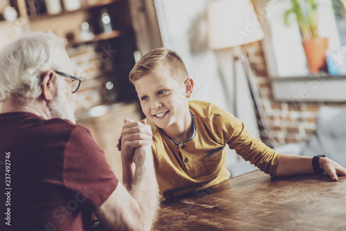 Photo  Pleased boy competing with his grandfather