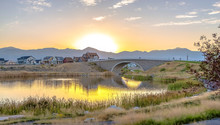 Bridge Over Oquirrh Lake With Golden Sun In Sky