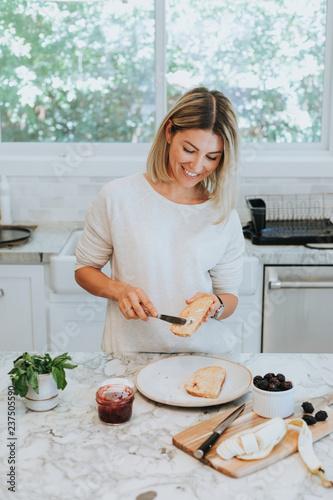 Woman spreading vegan cream cheese on a toast