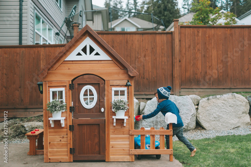 Fotografia, Obraz A little boy playing in his playhouse in the back yard.