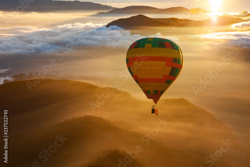 Fotografia hot air balloon flying over misty mountains at sunrise - freedom and travel conc