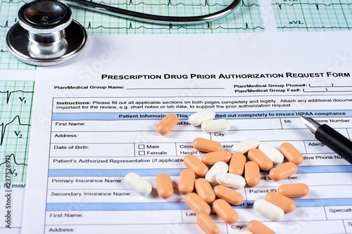 Photo Prescription drugs prior authorization request form, pills, stethoscope and pen on a EKG graph paper background