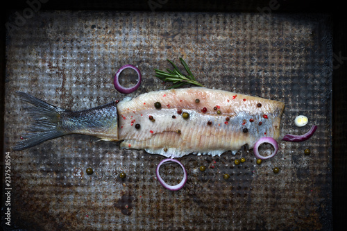Abstract herring fish with spices on old grunge metal plate creative still life