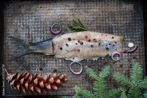 Abstract herring fish with spices and christmas ornament on metal plate creative still life