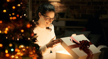 Woman Opening A Magical Christmas Gift
