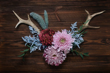 Antlers Decorated With Flowers On Rustic Wooden Background