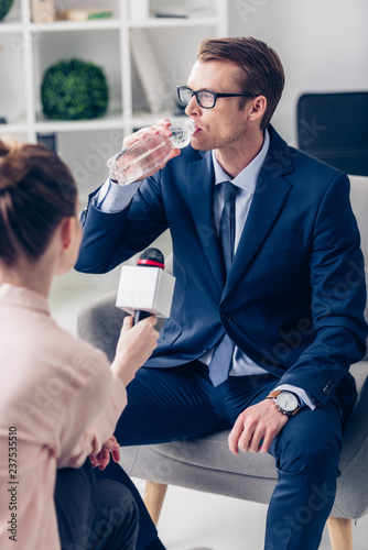 Fotografie, Obraz  handsome businessman drinking water while giving interview to journalist with mi