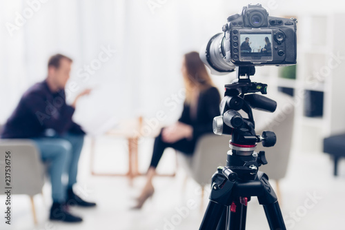 businesswoman in suit giving interview to journalist in office, camera on tripod Wallpaper Mural