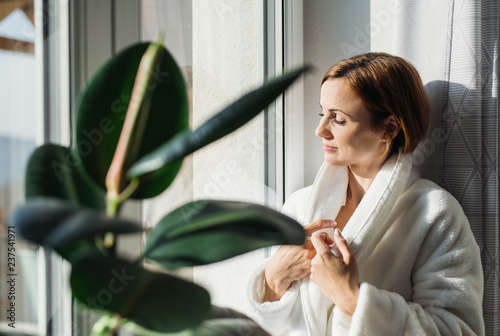 Fotografie, Obraz  A young woman with bath robe standing indoors by a window in the morning