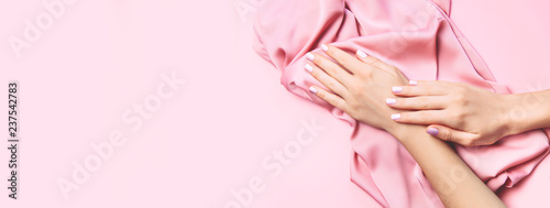 Manicure Beautiful woman manicure on creative pink background with silk fabric. Minimalist trend.