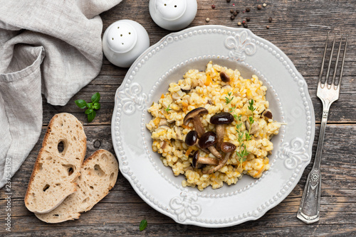 Pearl barley risotto with mushrooms on wooden background. Top view