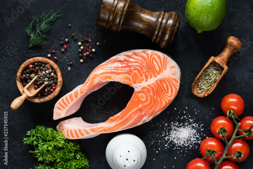 Raw salmon steak, vegetables and spices for cooking on black slate. Concept of cooking healthy food