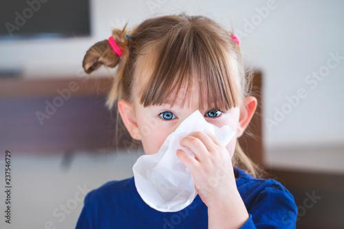 Fototapeta little girl blowing her nose into a handkerchief.