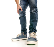 Man Legs Feet Jeans Sneakers On A White Background. Isolation