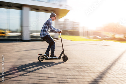 Young man in casual wear on electric kick scooter on city street in motion blur in sunday