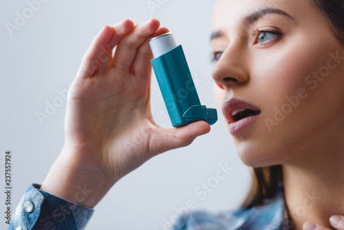 Obraz na plátně close-up view of young woman with asthma using inhaler