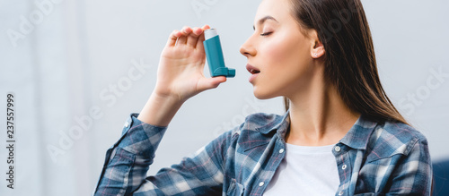girl using inhaler while suffering from asthma at home Fototapeta