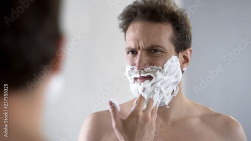 Valokuvatapetti Man preparing to shave, feeling discomfort and tingle on face from shaving foam
