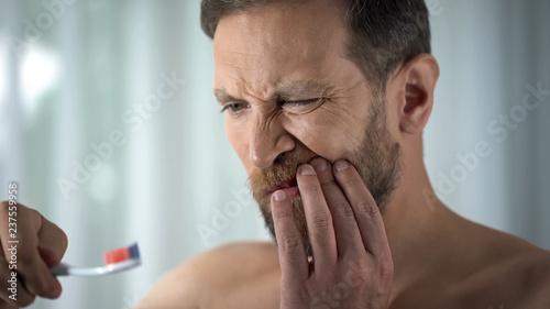 Fotografia Caucasian man brushing teeth and seeing blood on toothbrush, dental care, ache