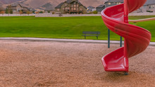 Red Spiral Slide With Mountain Homes And Lawn View