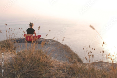 Fotografía  Beautiful view of woman doing yoga on the mountain with sea view at sunset