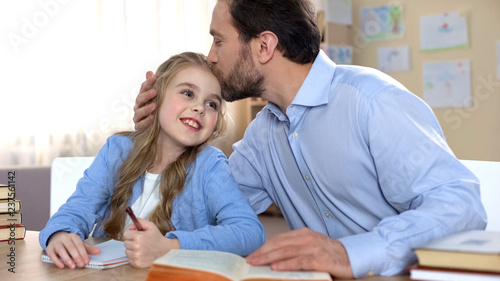 Proud father doing homework together with his daughter, education, family care Fototapeta