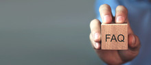 Man Holding FAQ Message On Wooden Cube. Frequently Asked Questions