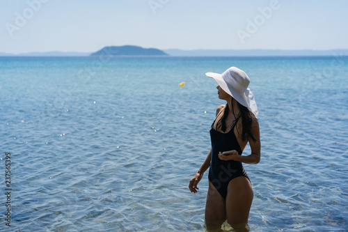 f02817ec5f38c Young girl in a bathing suit and a striped hat is standing in the blue sea