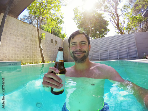 Happy young man relaxing with beer in a Pool Canvas Print