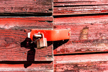 Macro Closeup Of Retro Vintage Red Wooden Barn, Shed Exterior With Locked Doors And Peeling Old Paint