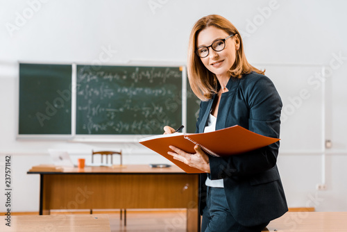 Obraz na plátně beautiful female teacher in formal wear writing in notebook and looking at camer
